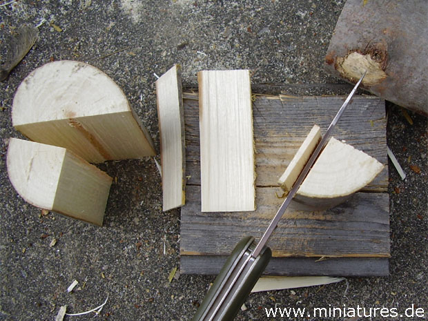 Using an old knife and a mallet, 2 inch boards are chopped off a quarter section of cordwood